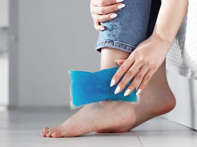 close-up-woman-feet-and-legs-and-hands-holding-ice-gel-pack-as-cold-compress-on-ankle-due-to_t20_b6kavm