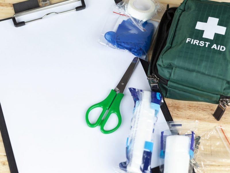 Green first aid kit on a wooden table with a clipboard and a pair of scissors and some dressings