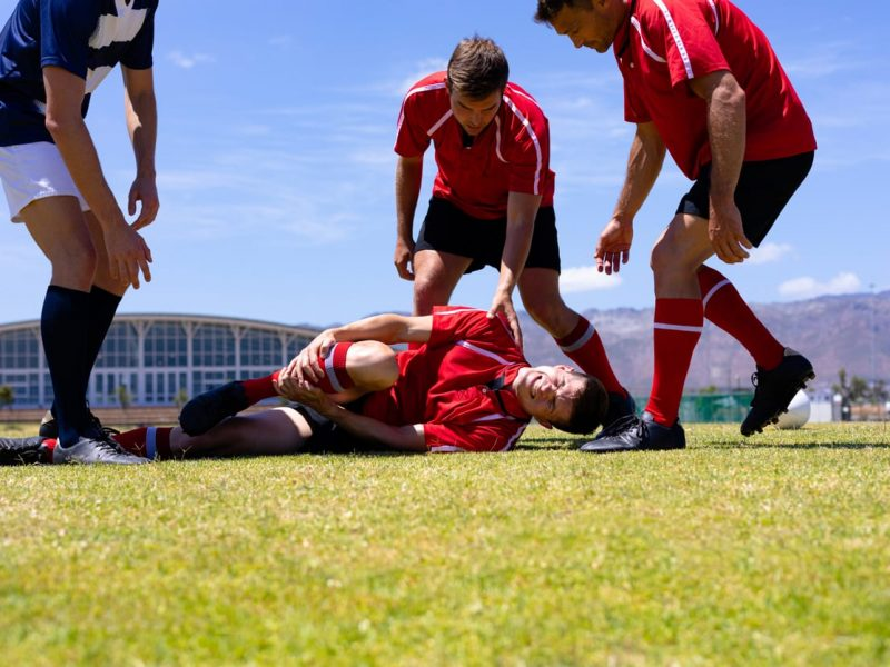 Low angle front view of a group of Caucasian male rugby players from opposing teams wearing team uniforms, gathered around an injured player lying the ground clutching his leg on a rugby pitch during a match, with blue sky in the background