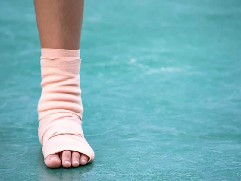 the-gauze-bandages-around-the-ankle-boy-and-leg-swelling-from-inflammation-on-a-green-background_t20_E40BwJ